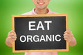 Eat organic text on blackboard held by smiling man in green background Royalty Free Stock Photography
