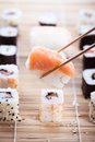 Eat sushi a salmon nigiri being picked up with chopsticks with different types of maki pieces on a wooden mat in the Stock Images
