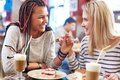 Eating cakes image of teenage girlfriends and talking in cafe Stock Photos