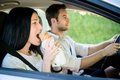 Eating in car couple men is driving and women is Royalty Free Stock Images