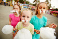 Eating cotton candy image of funny girls with posing on playground outdoors Royalty Free Stock Photography