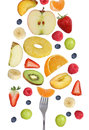 Eating falling fruits like apples fruit, oranges, banana and strawberry with fork Royalty Free Stock Photo