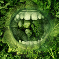 Eating green and healthy food concept with an open human mouth on a background of produce fresh vegetables as a symbol of Royalty Free Stock Photos