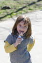 Eating ice cream a little girl and enjoying it Stock Photos