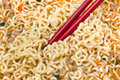 Eating instant noodles by red chopsticks of cooked close up Royalty Free Stock Images