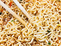 Eating instant noodles by wooden chopsticks of cooked close up Royalty Free Stock Photography