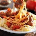 Eating spaghetti and meatballs with visible motion blur as a fork lifts up the noodles Stock Photo