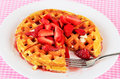Eating strawberry waffles bite taken from fresh strawberries sliced and spread over golden brown and sprinkled with powdered sugar Royalty Free Stock Images