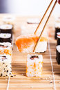 Eating sushi a salmon nigiri being picked up with chopsticks with different types of maki pieces on a wooden mat in the Royalty Free Stock Images