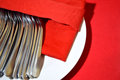 Eating utensilsstack of spoons on the red table Royalty Free Stock Photography