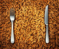 Eating wheat food as a health concept with a background of golden natural cereal grains and a place setting with a knife and fork Stock Images