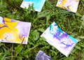Ebru painting by colorful paints. Bright abstract patterns on paper sheets on green grass. Royalty Free Stock Photo
