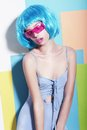 Eccentric extravagant woman in styled blue wig and pink sunglasses funny fashion model glasses Royalty Free Stock Photos