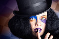 Eccentric mad fashion hatter in colourful makeup face portrait of a female wearing black top hat bright with black manicured nails Stock Photos