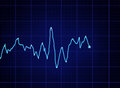 Ecg graph glowing blue on dark grid Stock Photo