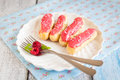 Eclair with cream and raspberry on a white plate on wood background Royalty Free Stock Photo