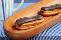 Eclairs on blue table cloth Stock Photos
