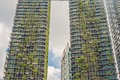 Eco architecture. Green skyscraper building with plants growing on the facade. Ecology and green living in city, urban environment