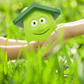 Eco cartoon house hands against spring green background family home concept Royalty Free Stock Photos