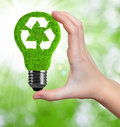 Eco energy bulb in hand on green background Royalty Free Stock Images