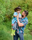 Eco farm. small boy child help father in farming. father and son in cowboy hat on ranch. kid in rubber boots. happy man Royalty Free Stock Photo