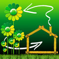 Ecologic house with green flowers wooden yellow meter tool forming a stylized and grass Royalty Free Stock Photo