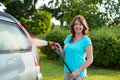 Ecological car wash woman washing her in garden without detergents in way Royalty Free Stock Photography