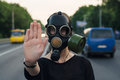 Ecological concept of air contamination woman in gas mask near highway showing stop gesture Royalty Free Stock Images