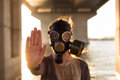 Ecological concept of air contamination woman in gas mask near water showing stop gesture Royalty Free Stock Images