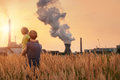 Ecological concept image father with son looking on chemical plant emissions at sunset time Royalty Free Stock Images