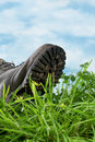 Ecological footprint large boot stepping in grass in extreme closeup symbol for Royalty Free Stock Photo