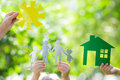 Ecology house in hands and family against spring green background Stock Photos