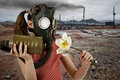 Ecology pollution little girl in gas mask smell big white flower Stock Images