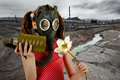 Ecology pollution little girl in gas mask smell big white flower Stock Photo
