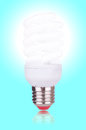 Economical bulb on blue background glowing Royalty Free Stock Image