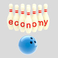 Economy conception as pins smashed by bowling ball downturn isolated on grey Royalty Free Stock Photo