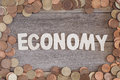 Economy the word money over a wooden surface and a lot of coins Stock Photo