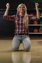 Ecstatic bowling women with raised hands winning woman at the alley young caucasian crouching down on her knees Royalty Free Stock Photos