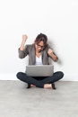 Ecstatic businesswoman raising her hands for corporate victory beautiful young or student relaxing sitting on the office floor Stock Photo