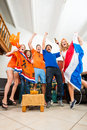 Ecstatic dutch fans sports cheer ecstatically over a goal and victory of the national team of the netherlands at home watching Royalty Free Stock Photos