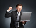 Ecstatic and enthusiastic businessman with laptop good news c chakka yieppieh Stock Photo