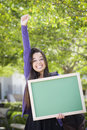 Ecstatic mixed race female student holding blank chalkboard portrait of an attractive excited and carrying backpack on school Royalty Free Stock Images