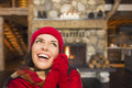 Ecstatic mixed race girl enjoying warm fireplace in rustic cabin smiling comfortable looking to the side Royalty Free Stock Images