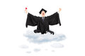 Ecstatic student holding diploma sitting on cloud and gesturing in graduation gown with in hand happiness isolated white Stock Photography