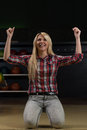Ecstatic women happy about the win winning bowling woman at bowling alley young caucasian crouching down on her knees Stock Photography