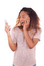 Ecstatic young african american woman making a phone call on her smartphone Royalty Free Stock Photography