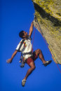 On the edge of danger ethnic climber dangles from his fingertips a challenging mountain peak Stock Photography
