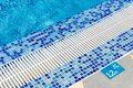 Edge of pool with indication of depth of 1.2 meters and sign that prohibits jumping Royalty Free Stock Photo