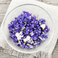 Edible violets in bowl foraged purple and white violet flowers from above square format Stock Photos