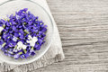 Edible violets in bowl foraged purple and white violet flowers on wood background with copy space Royalty Free Stock Photos